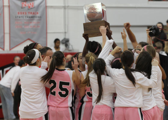The girls basketball team holds up their trophy after their victory against Niles North. Photo by: Vicky Robles