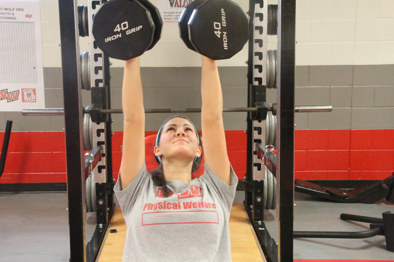 Senior Emily English presses 40-pound dumb bells during Varsity P.E. English plays volleyball. PHOTO by Rachael Kossy