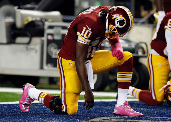 Washington Redskins quarterback Robert Griffin III bows his head in the end zone before the start of an NFL game against the Dallas Cowboys at AT&T Stadium in Arlington, Texas, on Sunday, October 13, 2013. (Richard W. Rodriguez/Fort Worth Star-Telegram/MCT)