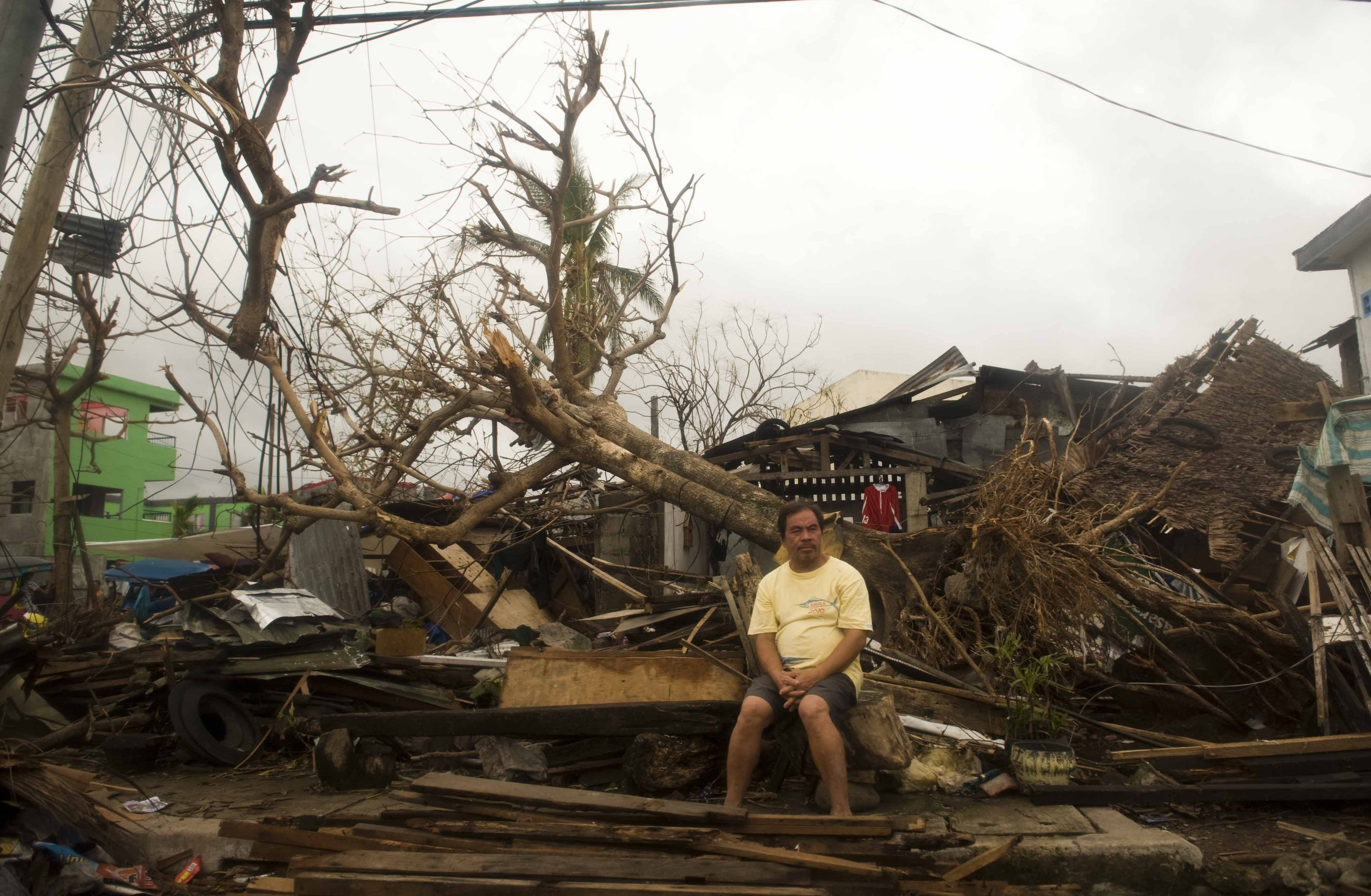 A resident sits on debris in typhoon-hit Leyte Province, Nov. 12, 2013. The United Nations said it had released $25 million in emergency funds to pay for emergency shelter materials and household items, and for assistance with the provision of emergency health services, safe water supplies and sanitation facilities. It's launching an appeal for more aid. (Lui Siu Wai/Xinhua/Zuma Press/MCT)