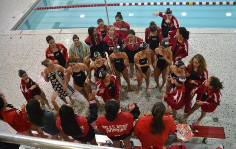 The girls swim team conversing during a meet.