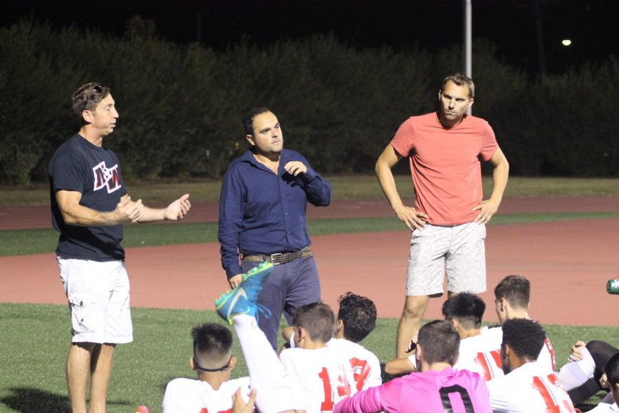 Assistant+Coach%C2%A0Vasilios+Papaioannou+%28far+left%29+speaks+to+the+varsity+boys+soccer+team+at+half+time+during+the+2017+season.+Photo+by+Sarah+Cohen.+