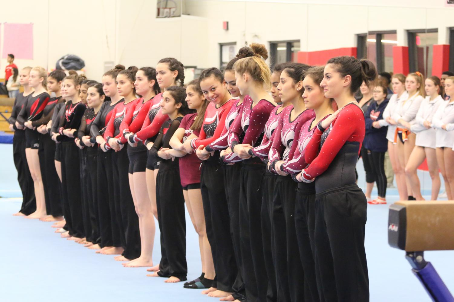 The varsity gymnastics team lines up for the National Anthem.