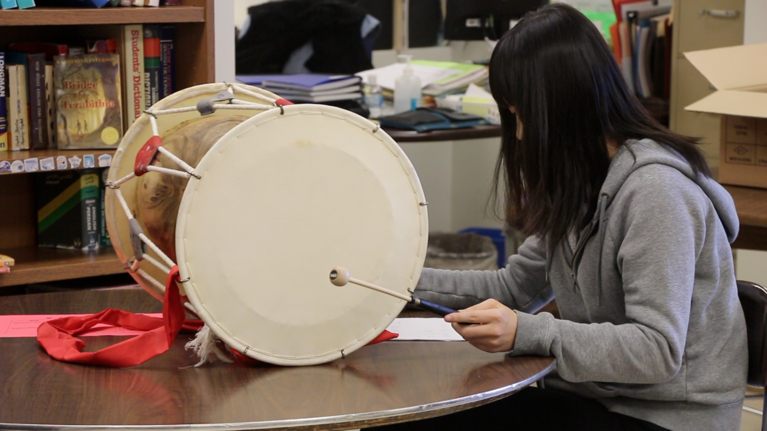 A student in Korean Club practices the traditional drums during a club meeting.