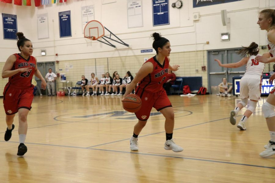 Junior Lidia Fakhoury brings the ball up the court to run a play.