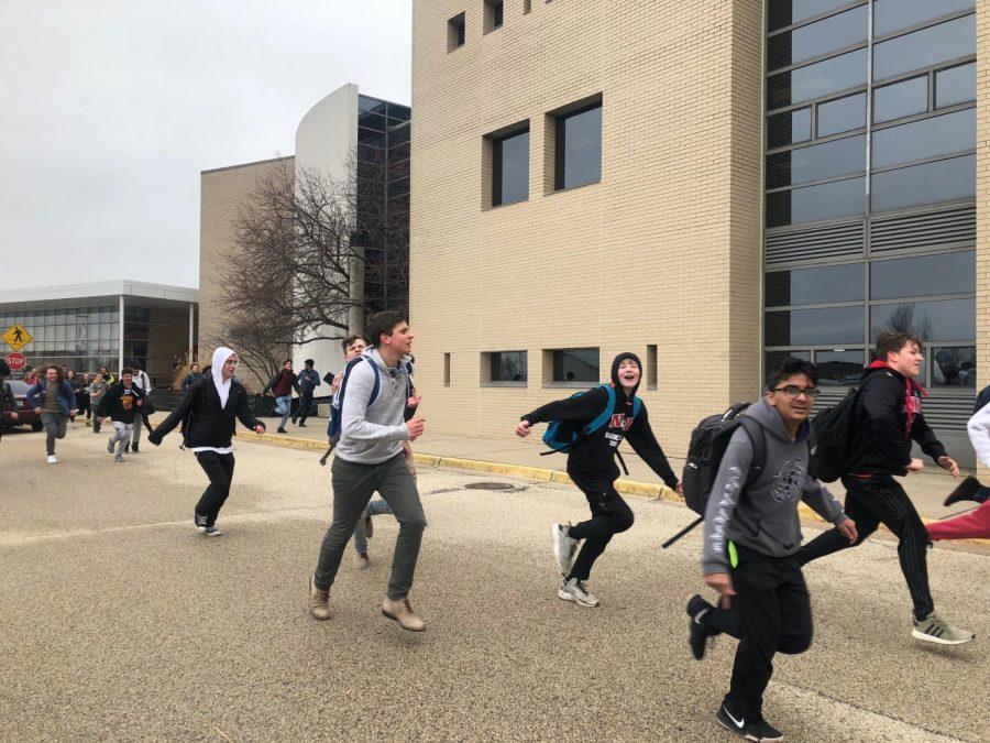 Students run towards the football stadium during the protest on Fri., Feb. 22.