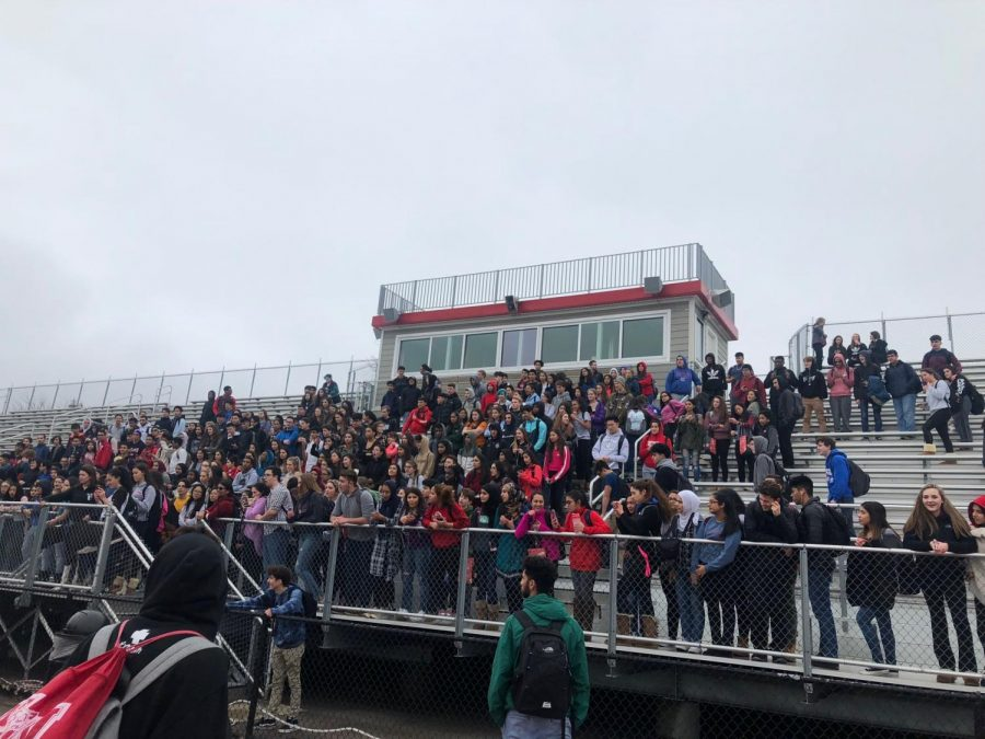 Students collectively group to protest on the bleachers.
