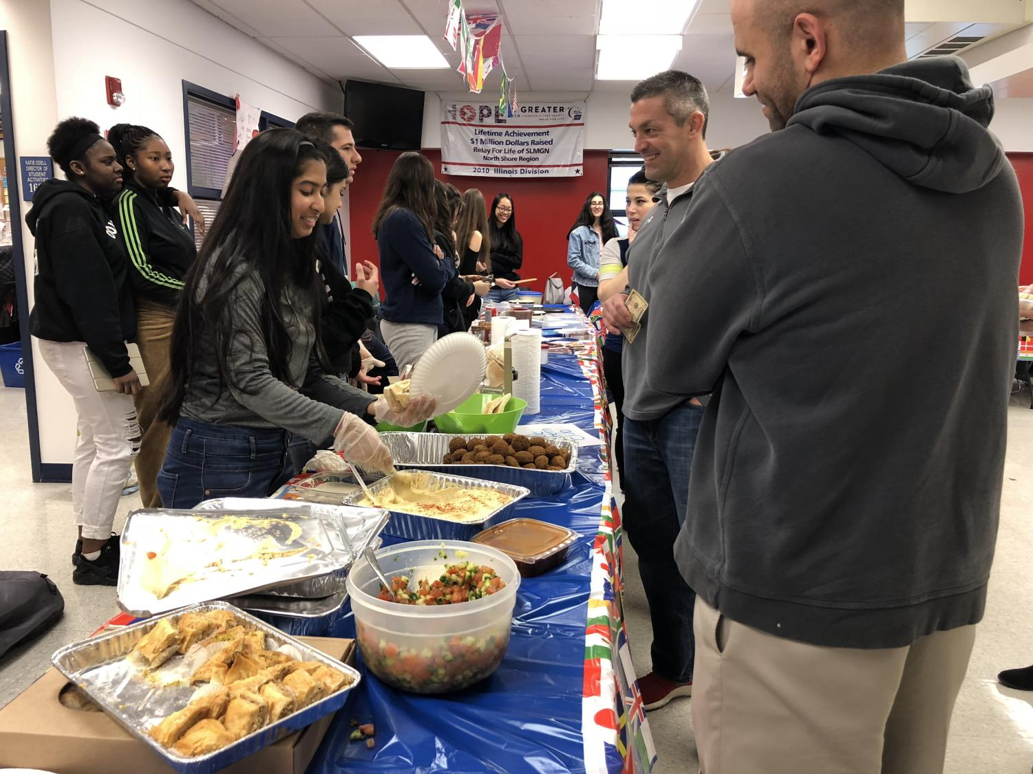 Student from Middle Eastern club serves food to Principal Jason Ness.