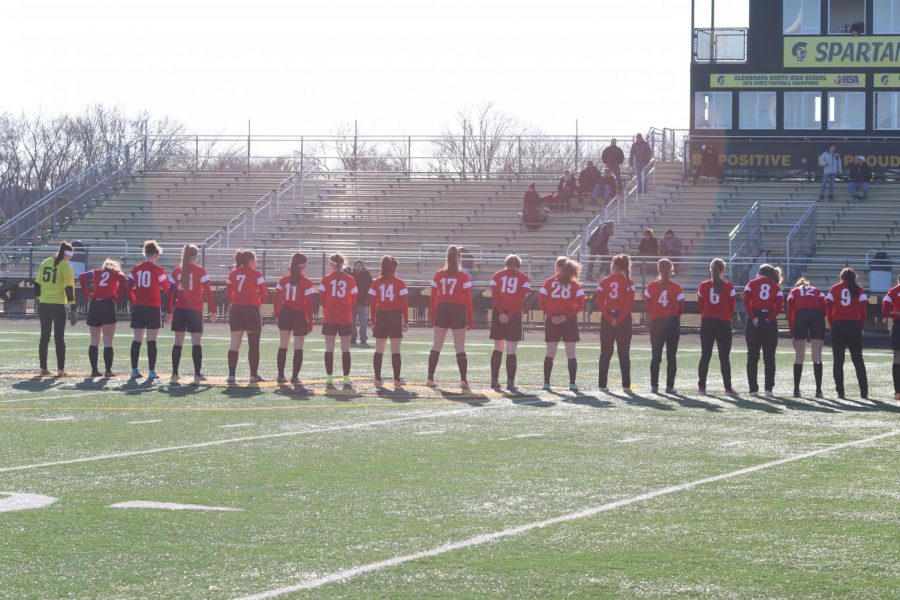 The girls varsity soccer team lines up for the National Anthem before their game.