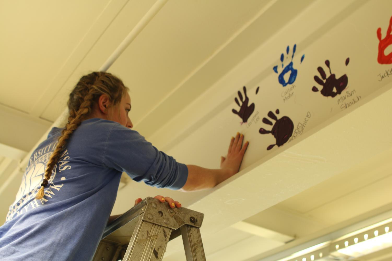 Senior Julia Karpilovsky leaves her mark on Niles West with her handprint.