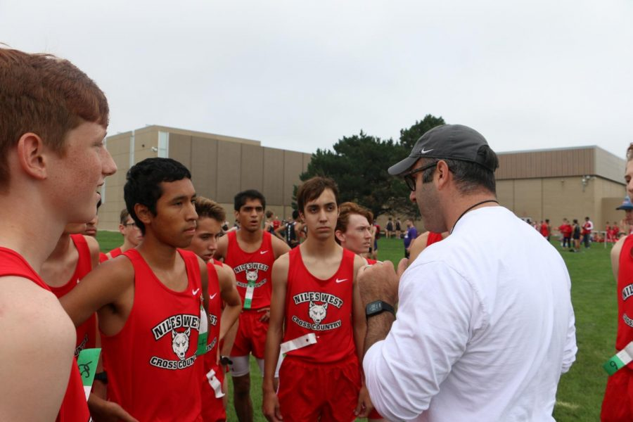Varsity+talking+with+coach+before+their+first+race+of+the+season.