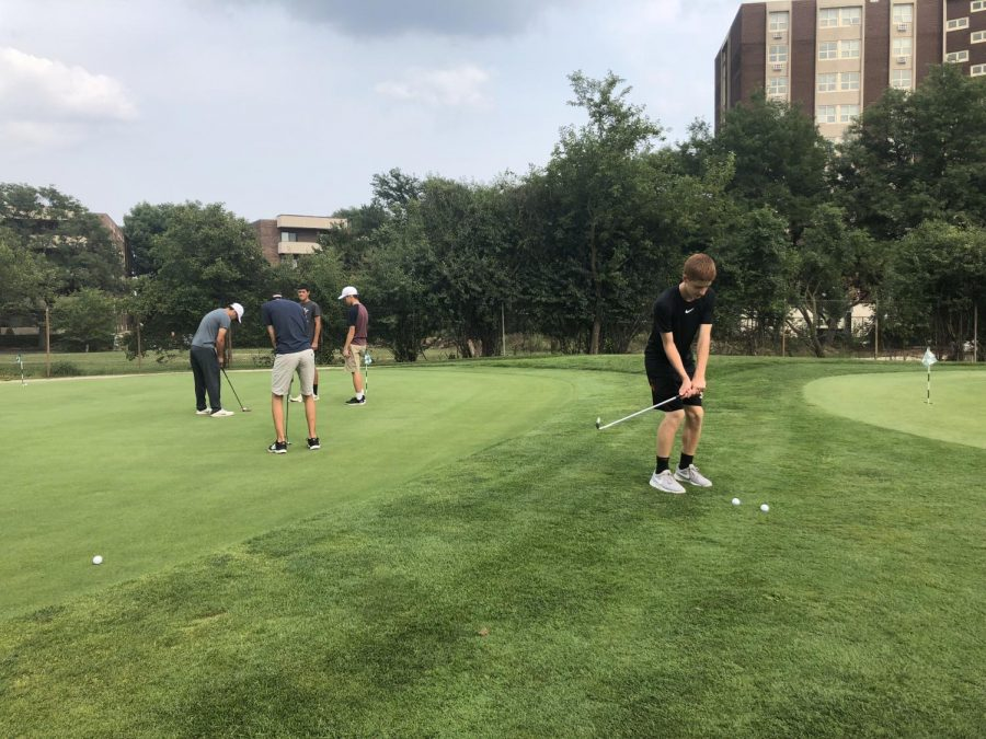 Varsity boys golf team practices puts on the green.