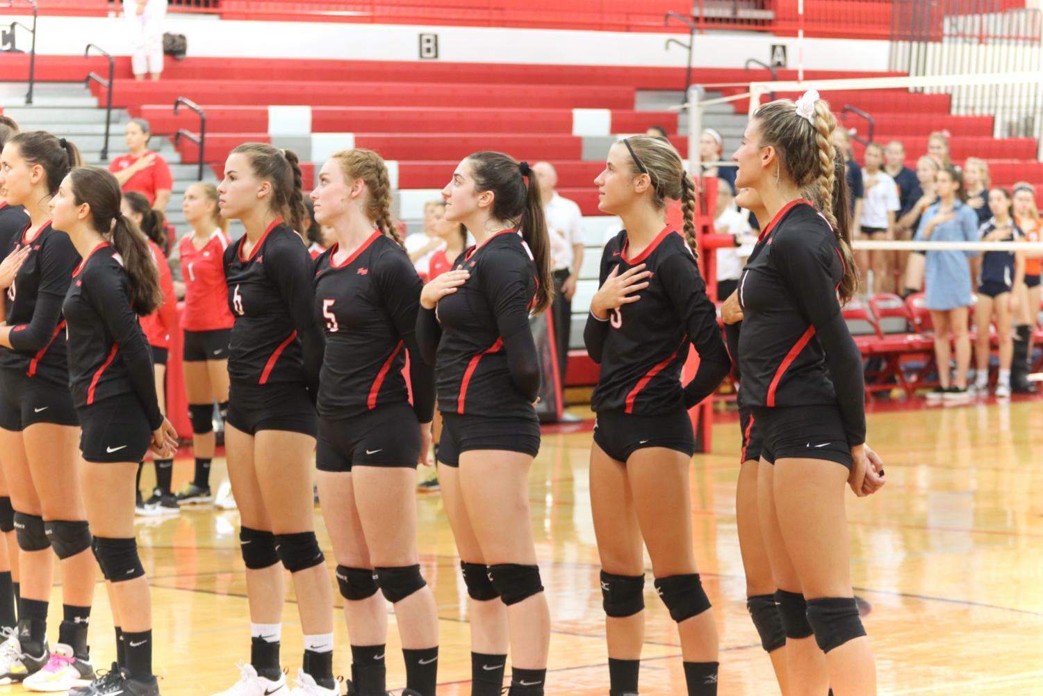 The Niles West Girls Volleyball team stands for the national anthem.