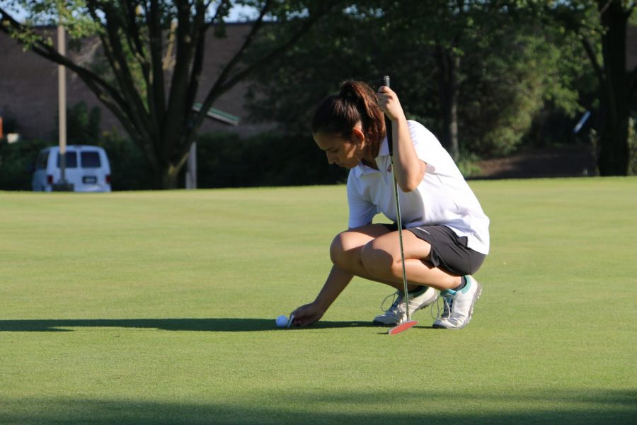 Klodiana Duraku repairing a pitch mark on the green.