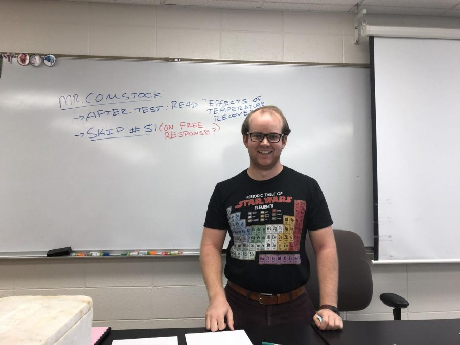 Physics teacher Anthony Comstock stands with a smile on his face before the start of class.