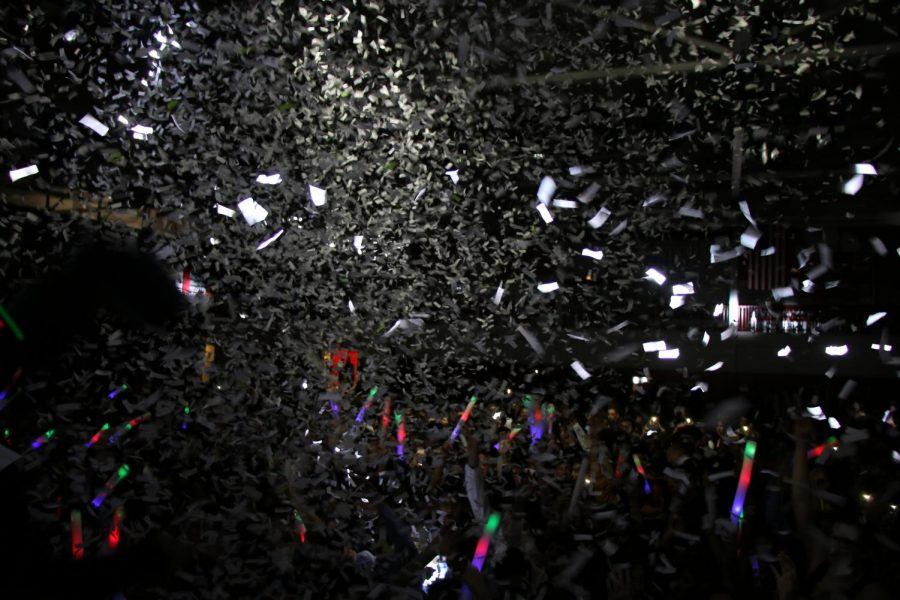 After distribution of large glow batons, confetti bursts from the stage and over the crowd.