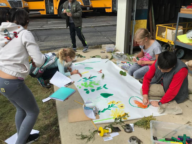 Edison elementary students sketch a mural of wild plants they identified at the Prairie site.