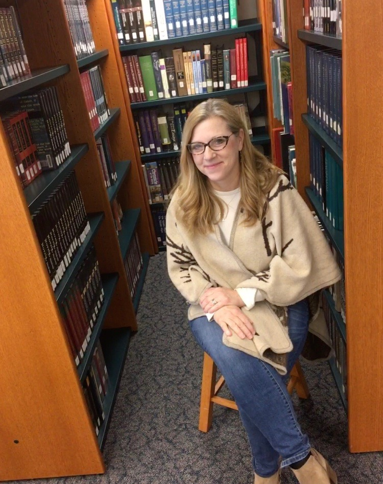 Amidst the books in the lit center, English teacher Sally Graham poses for a picture.