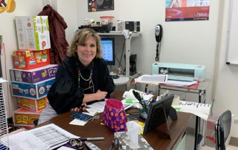 Mrs. Lisa Dunham posing at her desk during her fifth period Health Careers class.