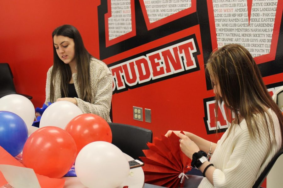 Senior Marina Bicanin and junior Andjela Dimitrijevic work on finalizing decorations before going to place them in the hallway.
