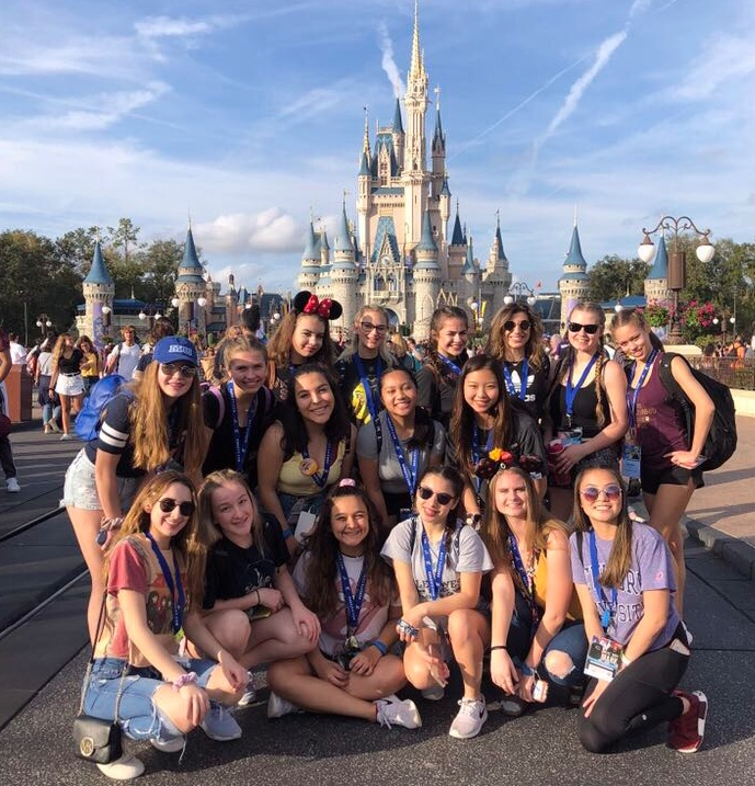The Poms team posing in front of Cinderella's castle at Disney World.