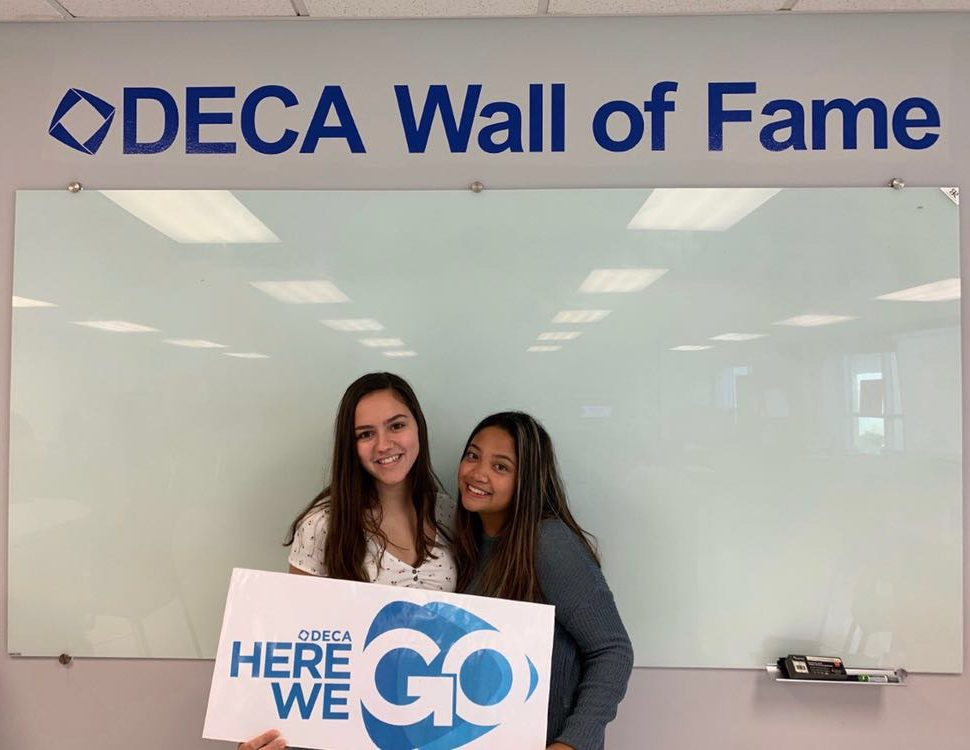 Seniors and DECAlicious 2019-2020 CEOs Caroline Schapmann and Meagan Mercado standing in front of the DECA Wall of Fame.
