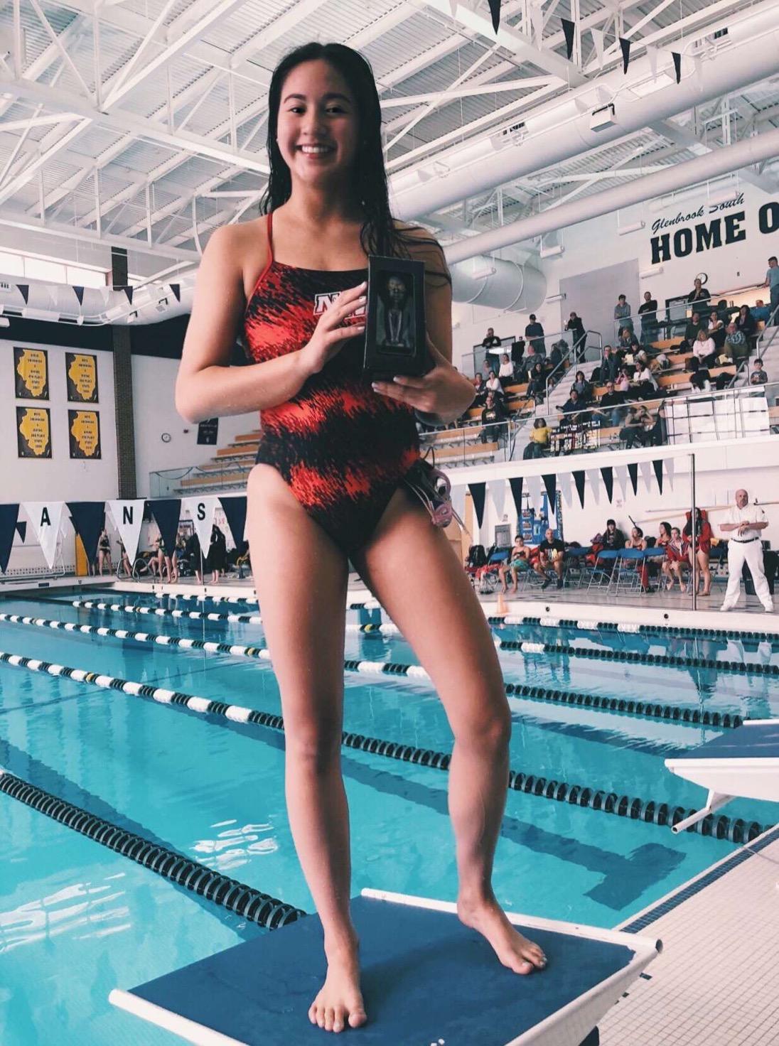 Junior Lian Fong posing after winning an award during her swim meet.