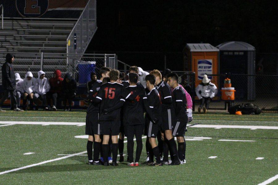 Niles West varsity boys soccer team in a huddle.