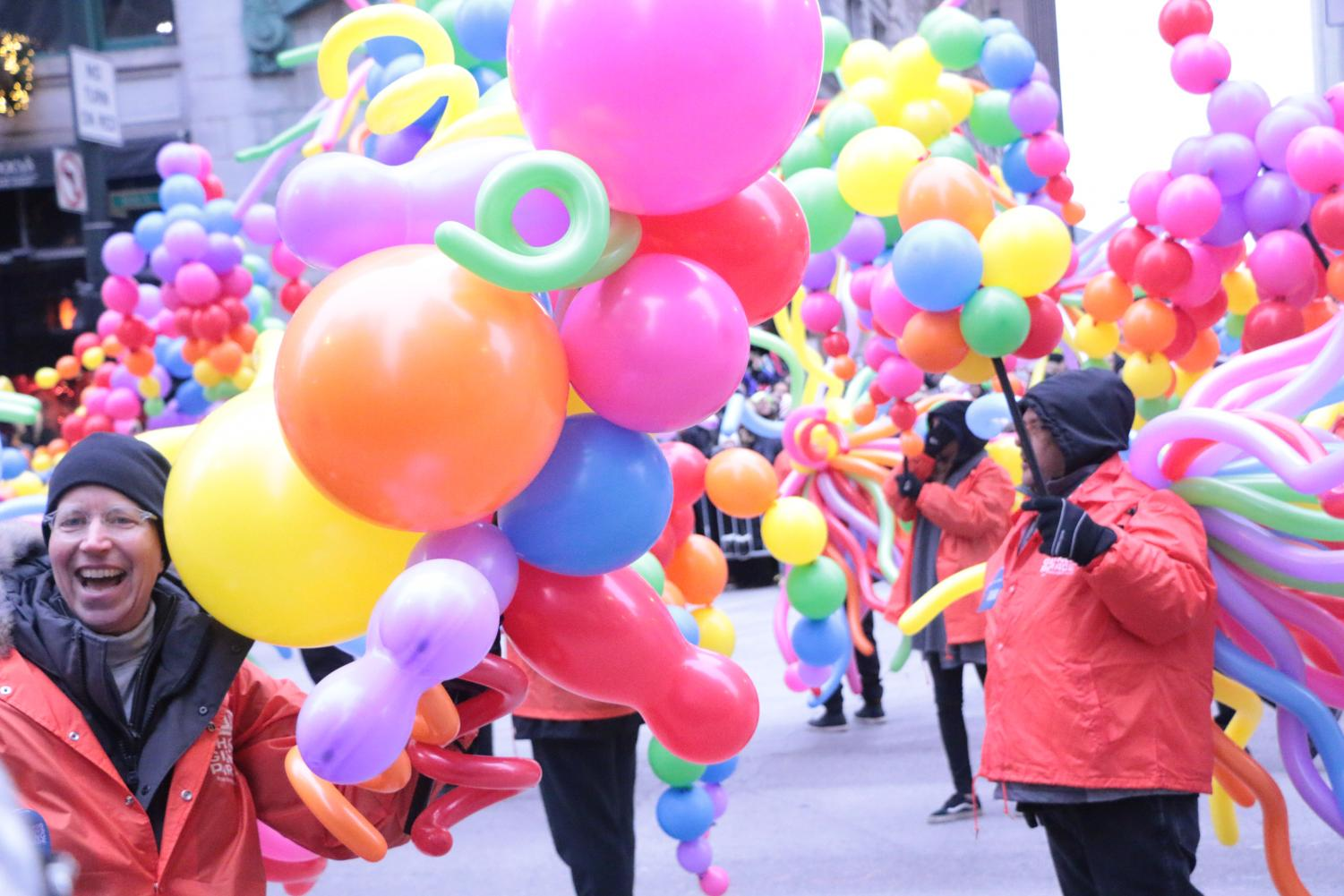Parade+volunteers+carrying+colorful+balloons+down+State+street.