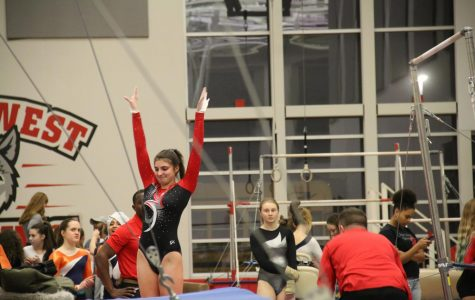 Senior Claire Adler landing after hitting her bar routine.