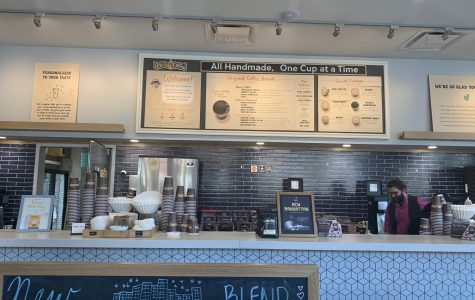 An overlook of the barista counter from the waiting line, with a complete display of the menu.