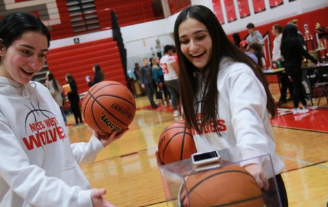 Junior Sami Lipsit and Albiona Ahmeti showing off their trophies as they recruit new basketball players.