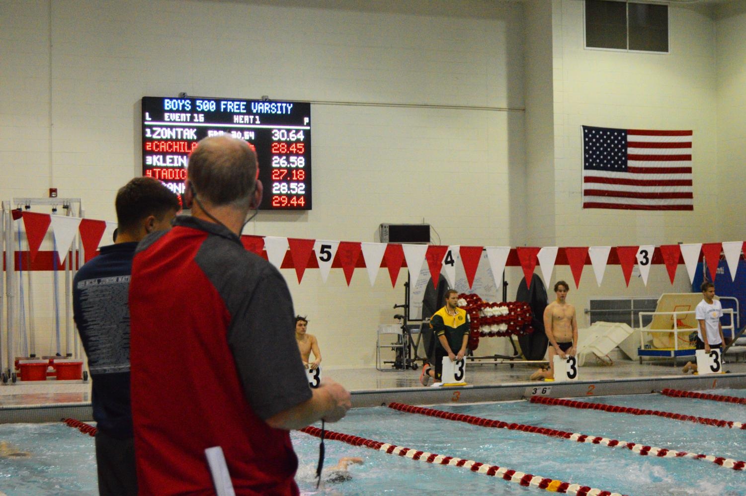 Varsity+swimming+coaches+keeping+track+of+their+players%27+times.+