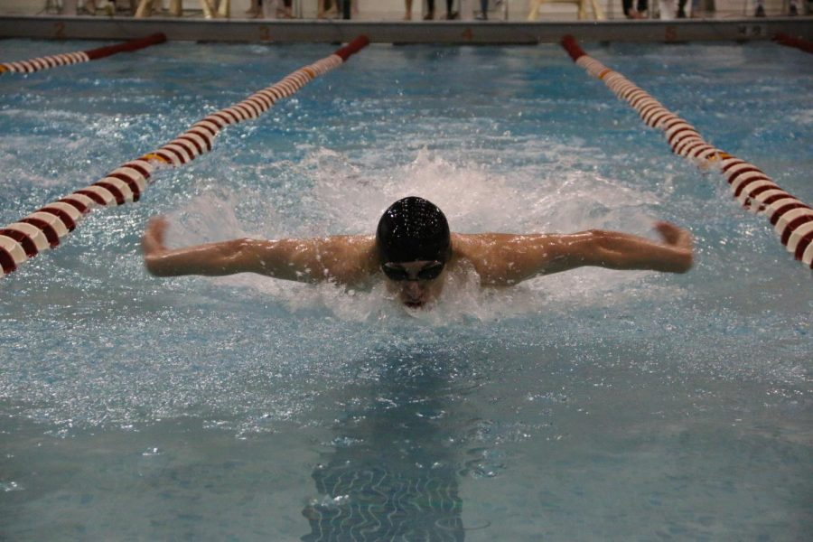 Senior Adrian Acosta in the middle of his 100 fly.