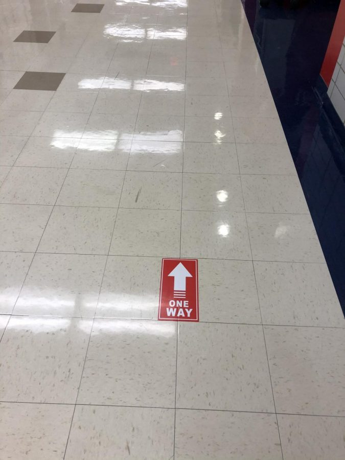 Hallway sign signaling that students can only go in one direction.